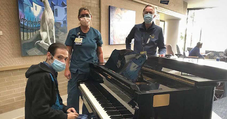 David Labelle playing on the piano with Greg Maxwell, music practitioner at Michigan Medicine.