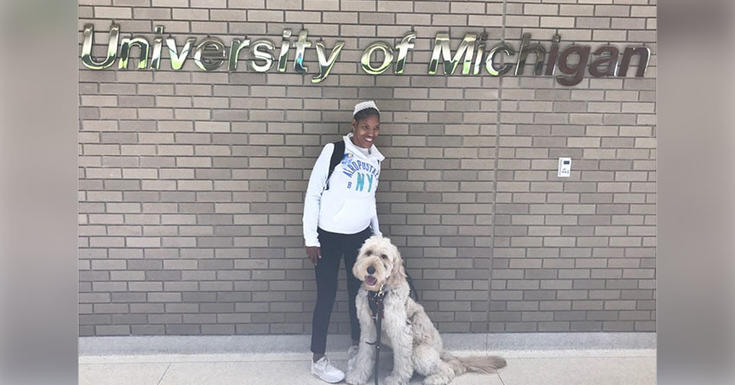 Young girl and dog in front of Michigan Medicine wall