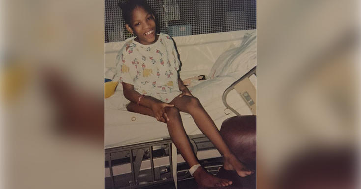 a young child in hospital gown on hospital bed smiling