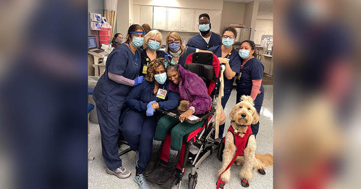 care team in navy scrubs hugging patient in wheelchair smiling