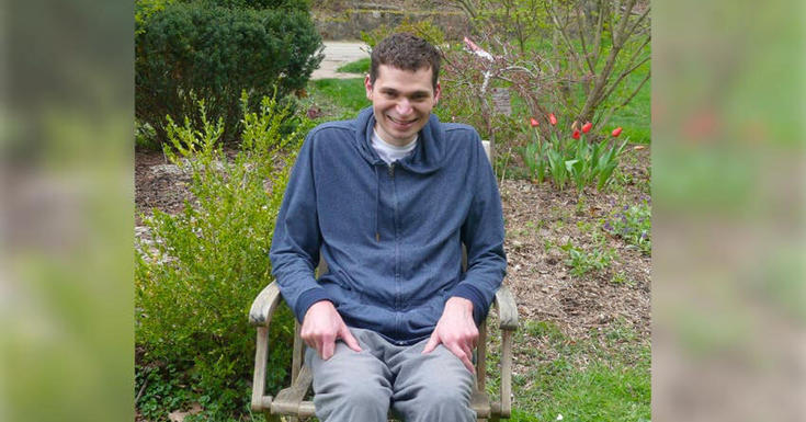 Man sitting in wheel chair by garden of flowers smiling