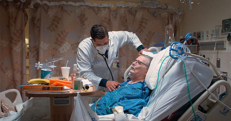 nurse standing at bedside with patient with mask on