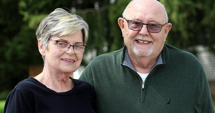 Senior couple standing outdoors smiling