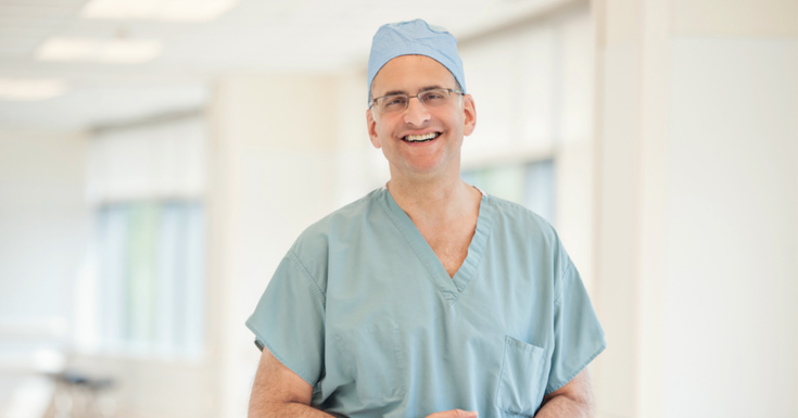 doctor smiling in blue teal scrubs at camera