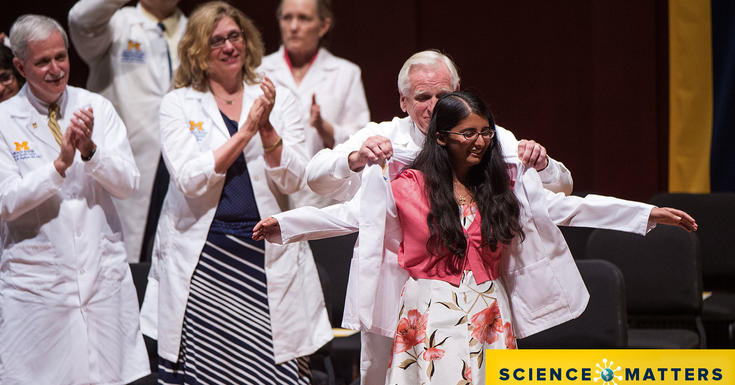 doctors' on stage in white coats putting white coat on female student facing crowd