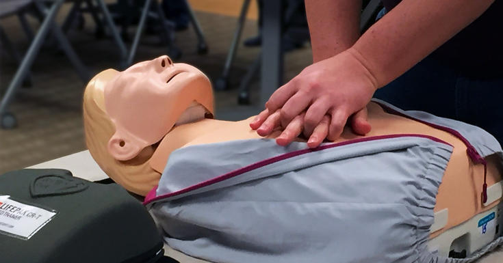 photo of hands on dummy mannequin chest indicating CPR