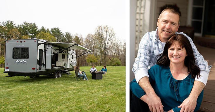 Man leaning over woman hugging and smiling near camper