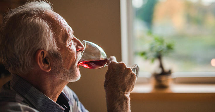 older man drinking red wine from glass