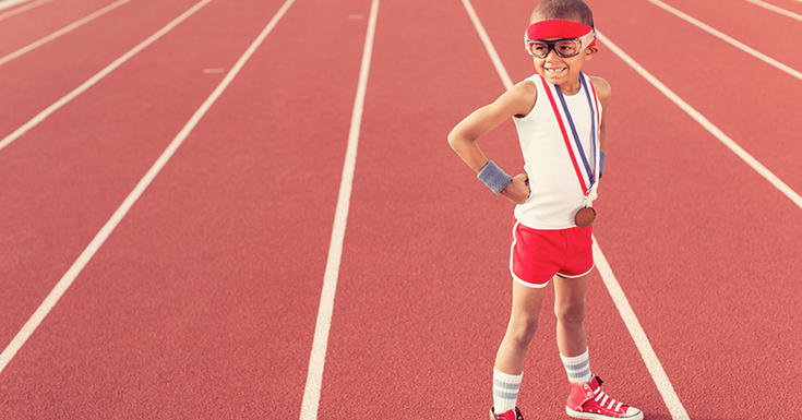 athlete boy in white shirt and red shorts on red track goggles medal