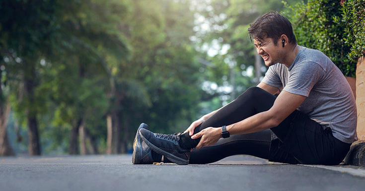 Man sitting on sidewalk among green trees holding his hurt ankle