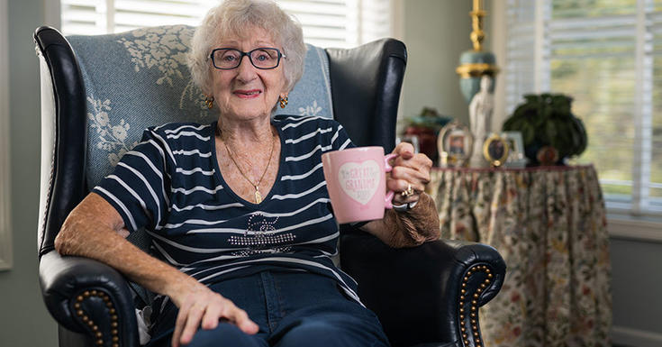 grandmother smiling with pink mug in hand in chair sitting