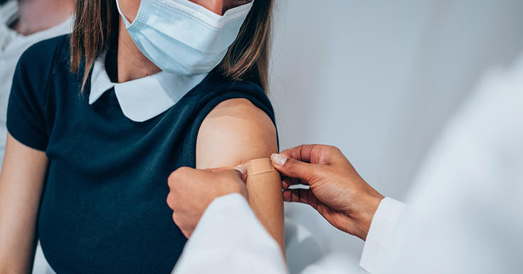 girl with navy shirt and white collar getting band aid put in arm with mask on
