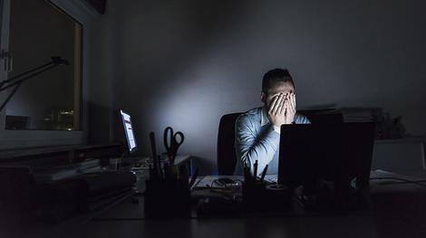 Man sitting behind a computer in a darkened room with his hands over his face