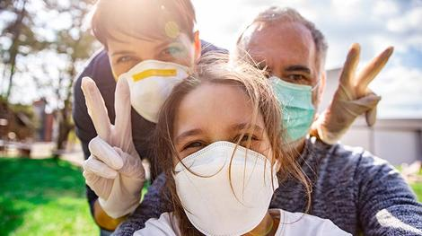 mom, dad and daughter taking selfie outside with peace signs and masks on