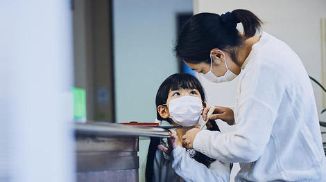 Mother and child with masks at doctors